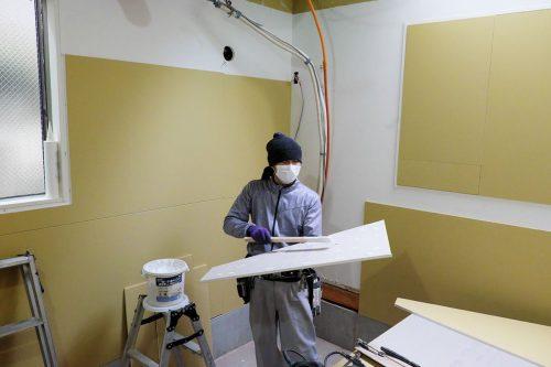壁にボード貼る作業